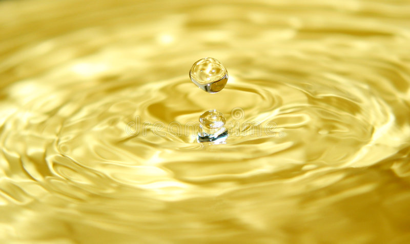 Oro liquido e una goccia immagini stock