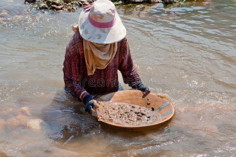Oro que se lava de la mujer en el río imagen de archivo