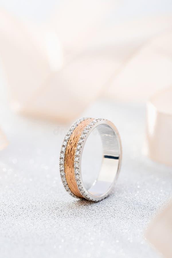 Oro rosa alla moda e fede nuziale d'argento con superficie e le pietre preziose strutturate immagine stock libera da diritti