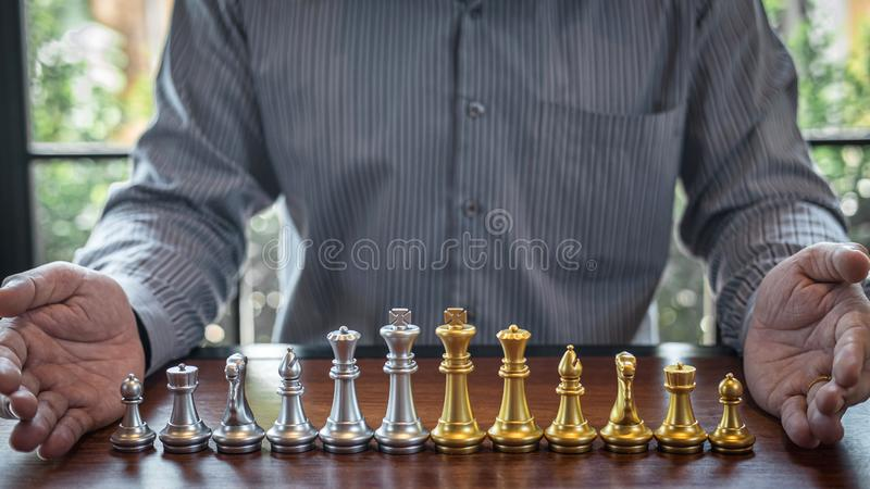 Oro y ajedrez de plata con el jugador, hombre de negocios inteligente que juega la competencia del juego de ajedrez al negocio de foto de archivo libre de regalías