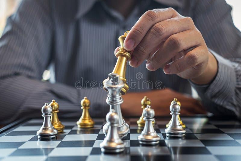Oro y ajedrez de plata con el jugador, hombre de negocios inteligente que juega la competencia del juego de ajedrez al negocio de fotos de archivo