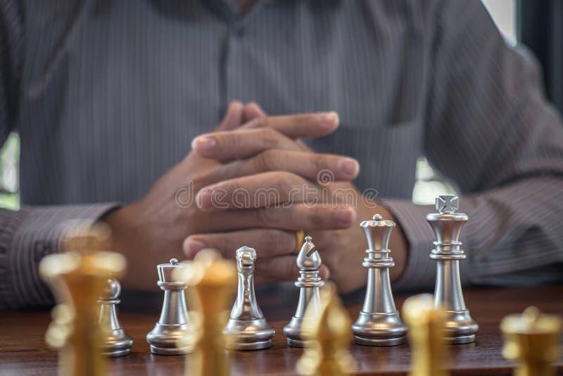 Oro y ajedrez de plata con el jugador, hombre de negocios inteligente que juega la competencia del juego de ajedrez al negocio de imagenes de archivo