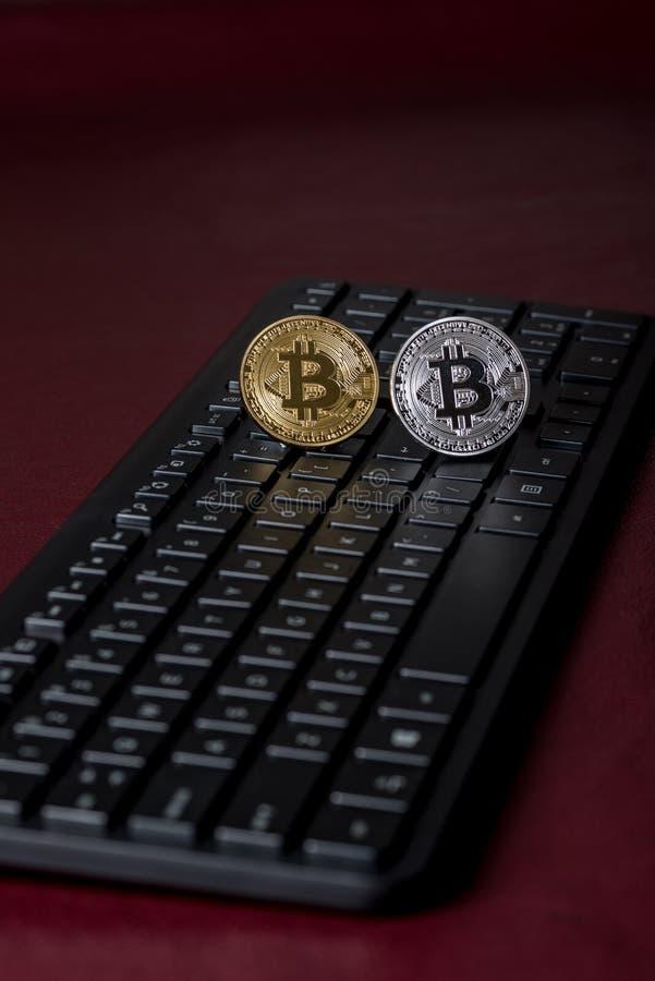 Oro y plata Bitcoin en un teclado de ordenador imagenes de archivo