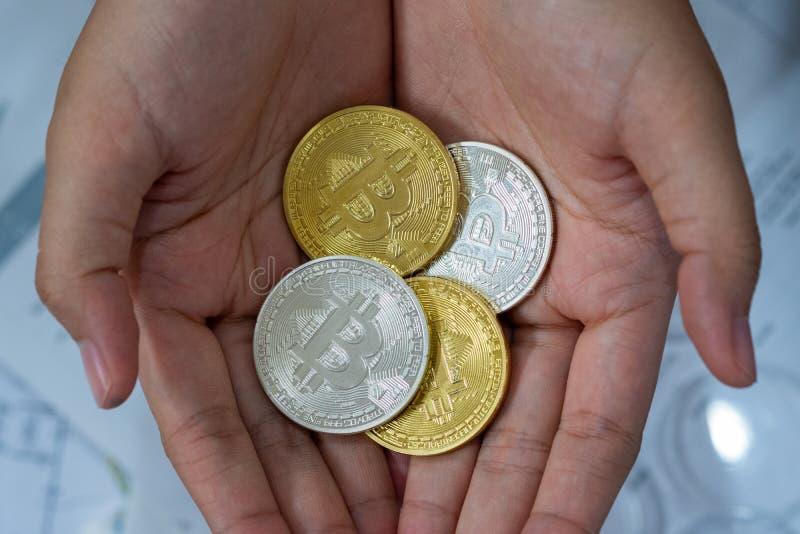 Oro y plata Bitcoins que se sostiene a disposición, concepto manry y del cryptocurrency virtual imagen de archivo libre de regalías