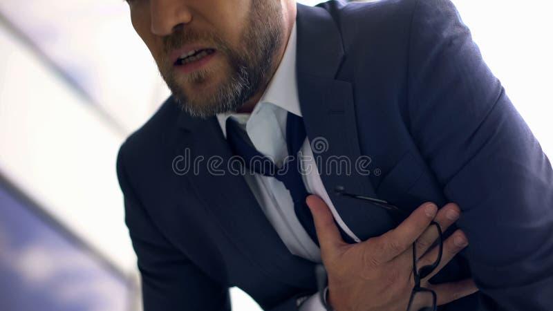 Oroad bröstkorg för känsla för kontorsarbetare att smärta, överansträngd chef, hjärtinfarkt arkivfoto