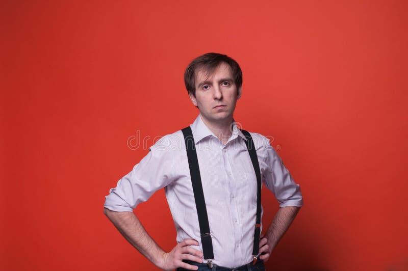 Oroad man med händer på höfter i rosa skjorta och svarta suspenderen som ser kameran på orange bakgrund royaltyfria foton