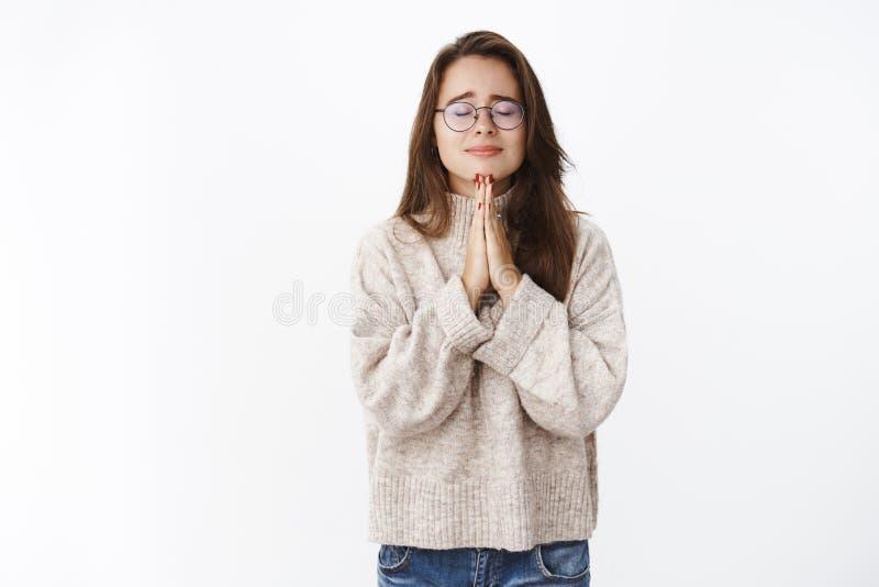 Oroat och otryggt ber rynka pannan för flickakänsla vara emotionellt som nära ögon som rymmer händer i och att göra att be för ön arkivfoton