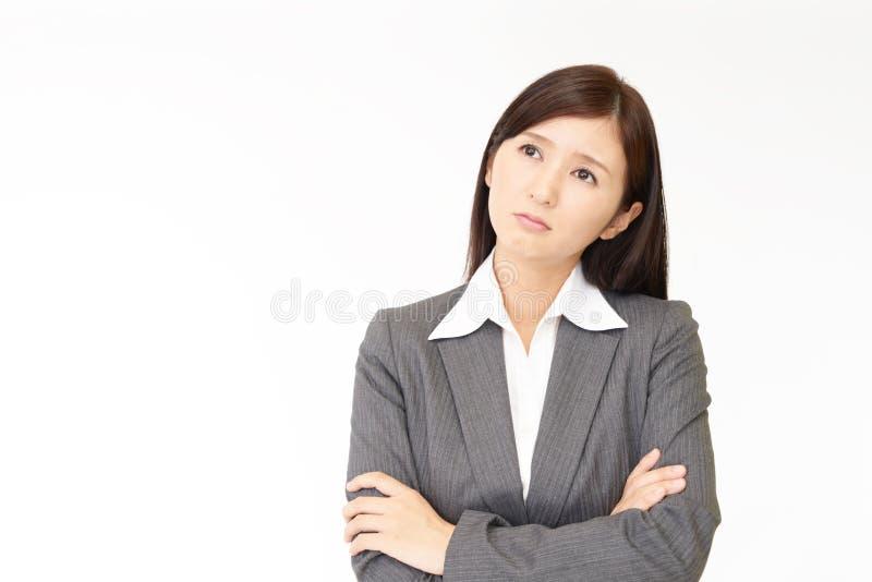 Orolig asiatisk affärskvinna arkivbild
