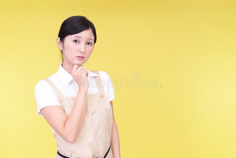 Orolig asiatisk kvinna i förkläde arkivfoto