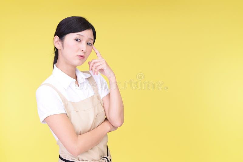 Orolig asiatisk kvinna i förkläde royaltyfria bilder