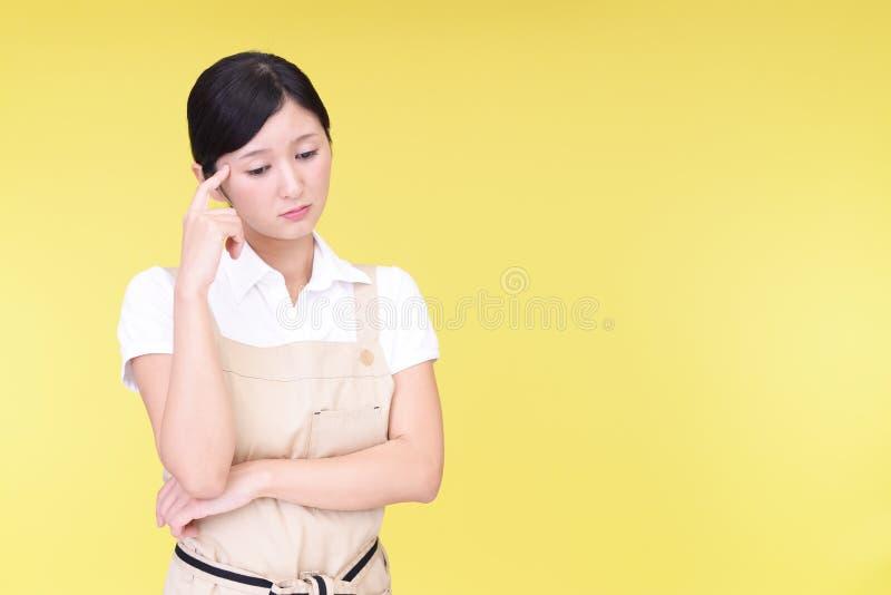 Orolig asiatisk kvinna i förkläde fotografering för bildbyråer