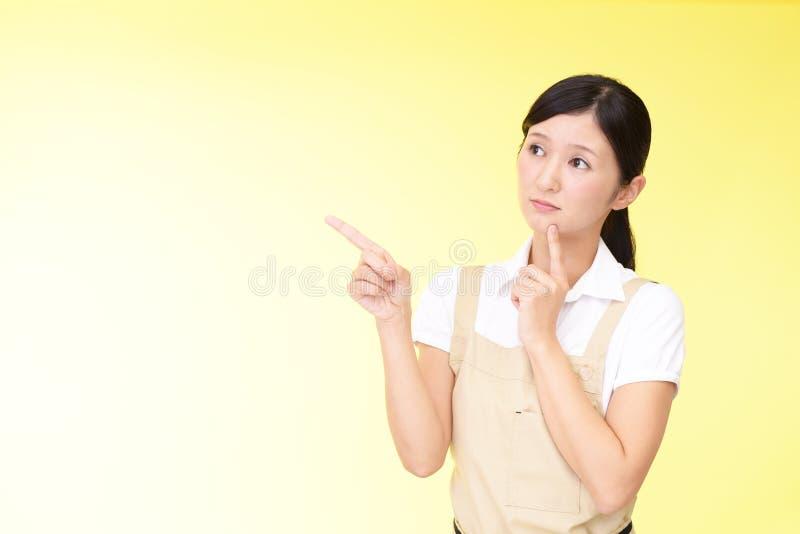 Orolig asiatisk kvinna i förkläde royaltyfri fotografi