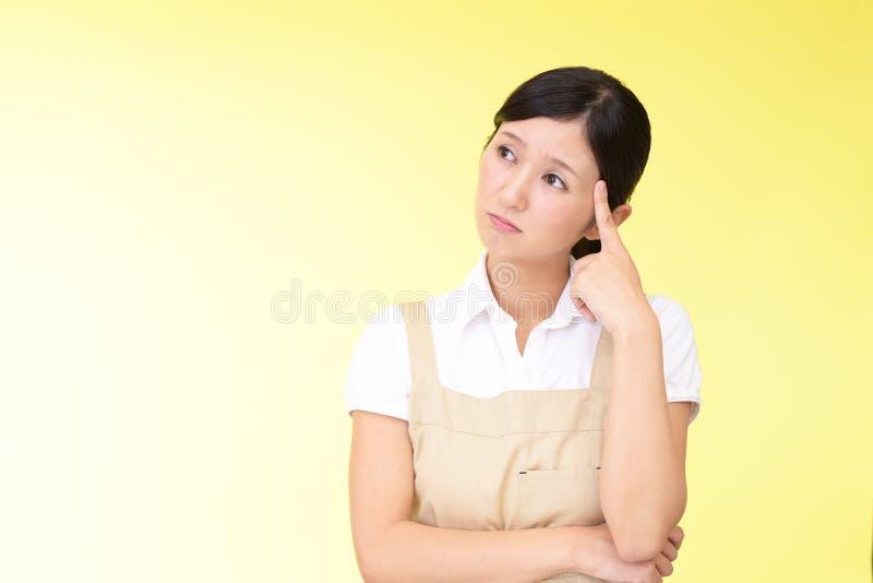 Orolig asiatisk kvinna i förkläde royaltyfri foto