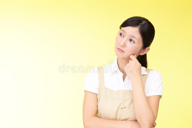 Orolig asiatisk kvinna i förkläde arkivbild