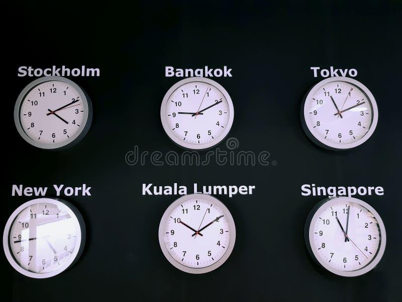Orologi di parete che mostrano periodo differente di molte città nel mondo sul fondo nero della parete fotografia stock libera da diritti