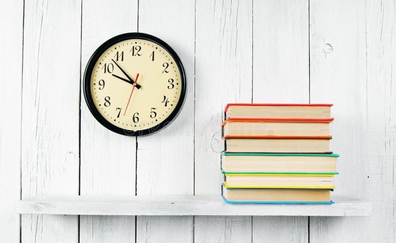 Orologi e libri su uno scaffale di legno fotografie stock libere da diritti