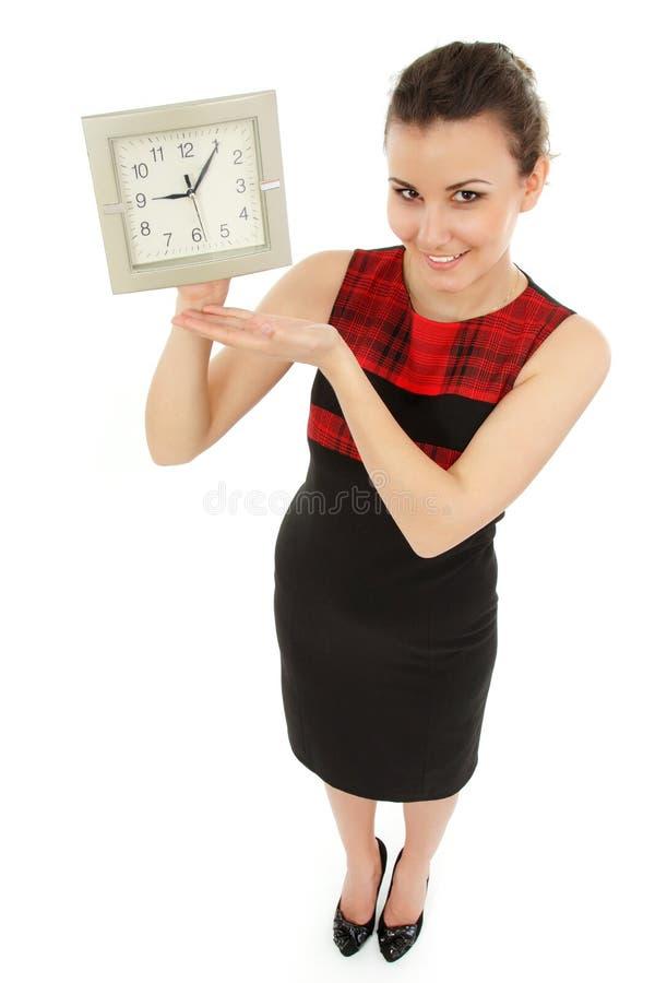 Orologio allegro della tenuta della donna di affari isolato su bianco immagine stock