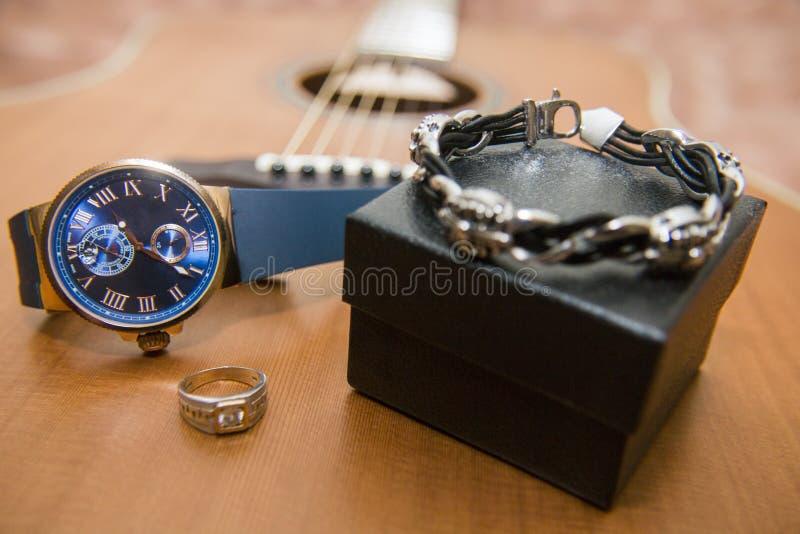 Orologio, anello di oro, braccialetto e chitarra acustica nei precedenti fotografie stock
