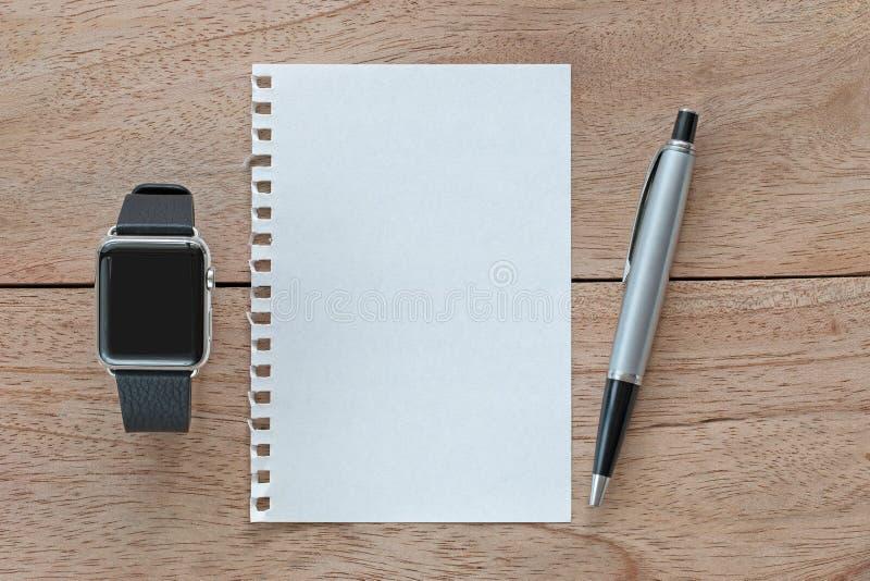 Orologio astuto con le bande di cuoio, il Libro Bianco in bianco e la penna dell'argento fotografie stock