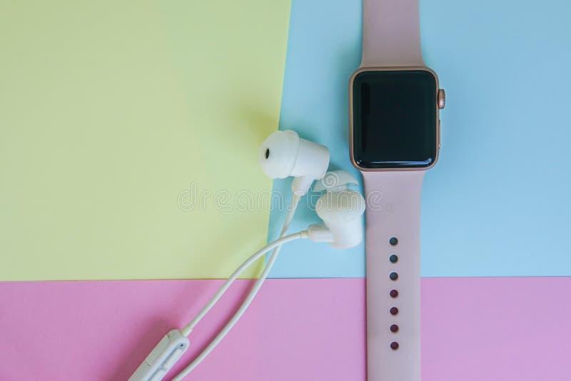 Orologio astuto con le cuffie bianche senza fili nel fondo minimo blu e giallo di rosa pastello fotografia stock libera da diritti