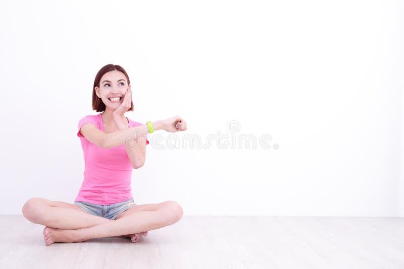 Orologio astuto di sembrare della donna di sorriso immagini stock