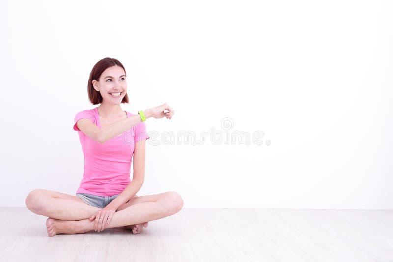 Orologio astuto di sembrare della donna di sorriso fotografia stock libera da diritti