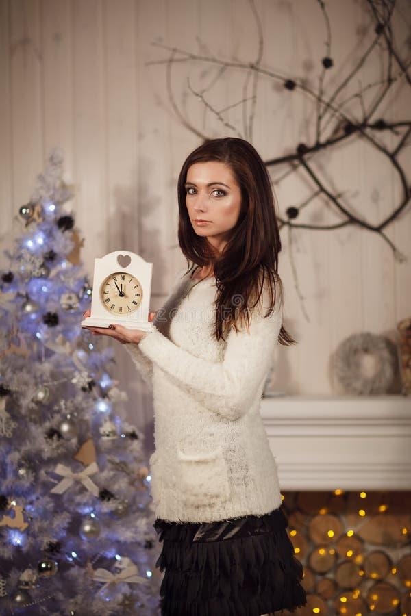 Orologio attraente della tenuta della giovane donna vicino all'albero di Natale immagini stock