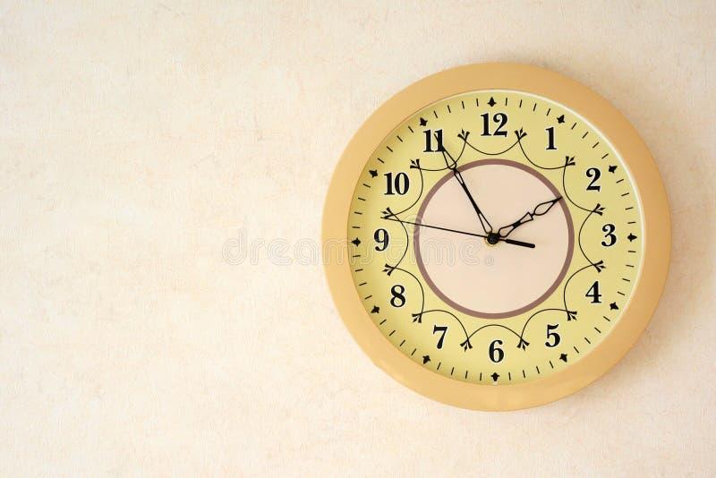 Orologio beige sulla parete Foto con spazio per testo immagini stock libere da diritti