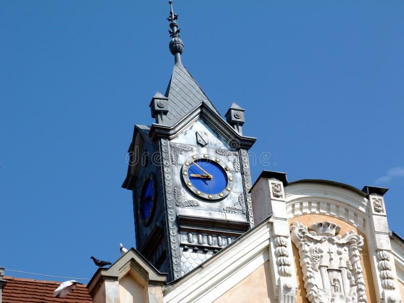 Orologio blu semplice della torre di retro stile con le mani gialle nella facciata del metallo di colore dello zink immagini stock libere da diritti