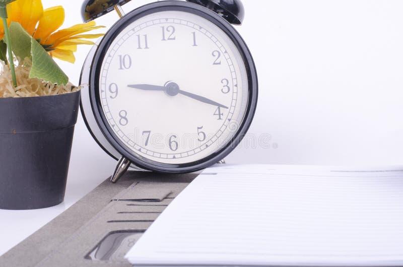Orologio d'annata e diario sulla tavola sopra la parete bianca del fondo fotografia stock