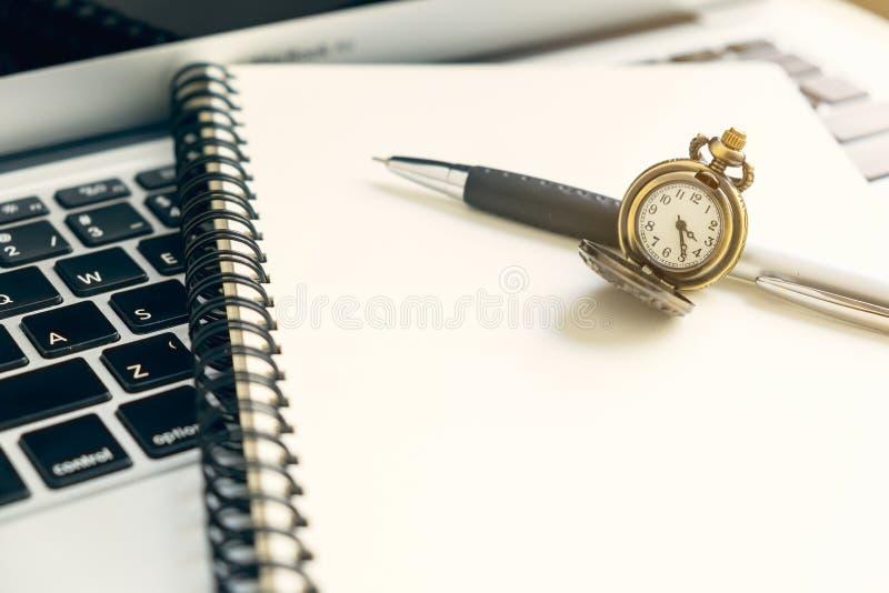 Orologio d'annata sul taccuino aperto di spirale e penna sopra il computer portatile fotografie stock