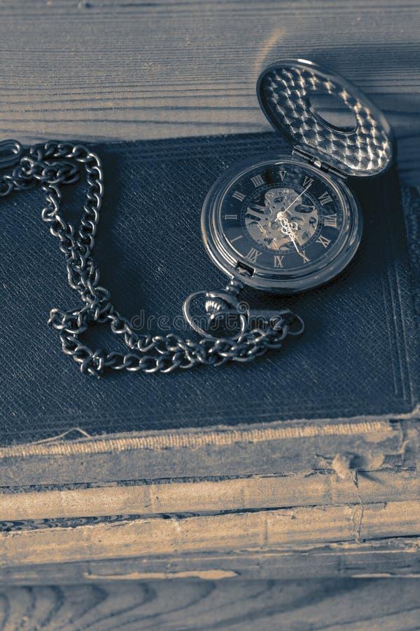 Orologio da tasca antico della tasca con una catena su una pila di vecchi libri Su una priorit? bassa di legno fotografia stock libera da diritti