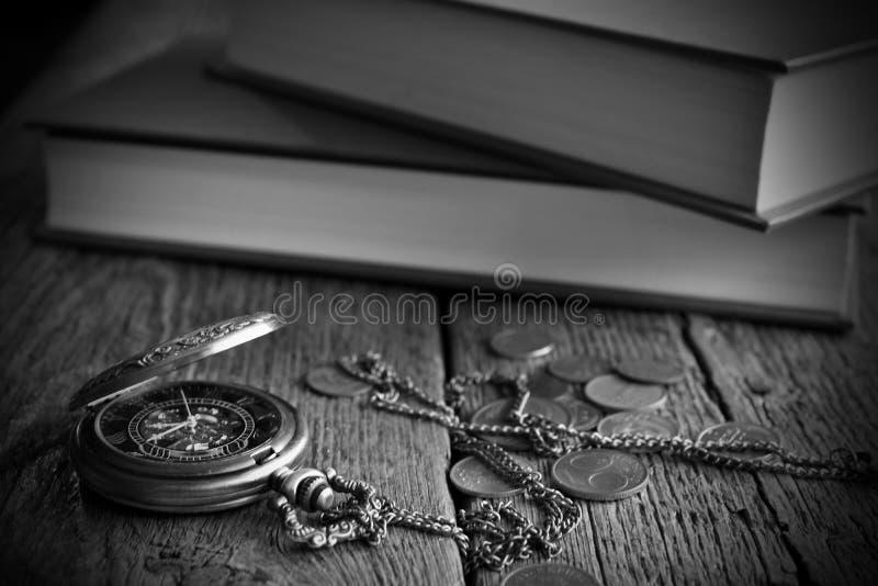 Orologio da tasca antico, libri e vecchie monete immagini stock libere da diritti
