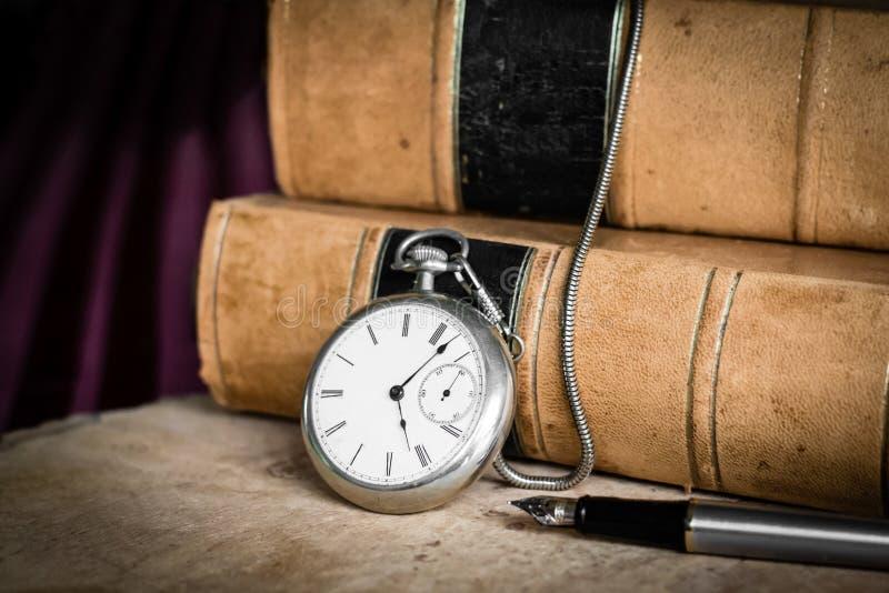 Orologio da tasca antico su legno burled con i vecchi libri rilegati e penna stilografica di cuoio immagini stock libere da diritti