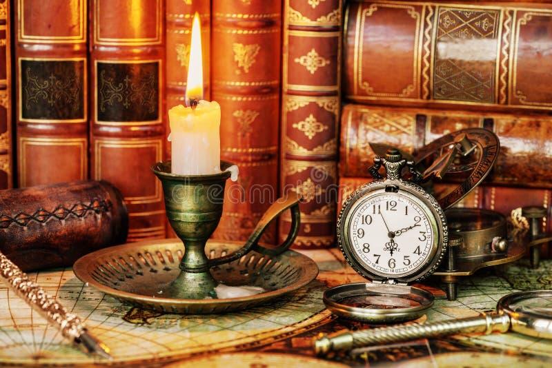 Orologio da tasca, candela bruciante e vecchi libri immagine stock libera da diritti