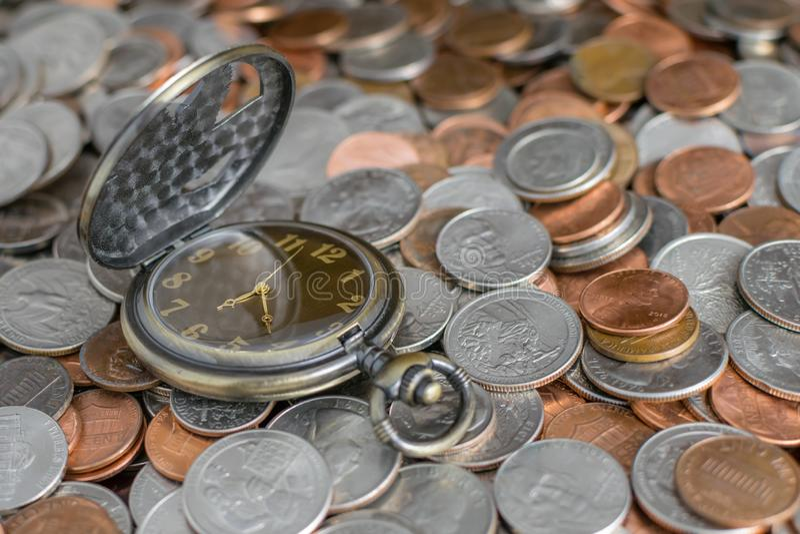 Orologio da tasca classico con il fondo dei soldi della moneta; Il tempo è denaro concetto, valore di periodo di soldi TVM immagini stock