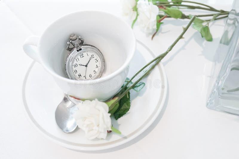 Orologio da tasca d'annata Un chiuso su di un tazza da the con pocke antico immagini stock