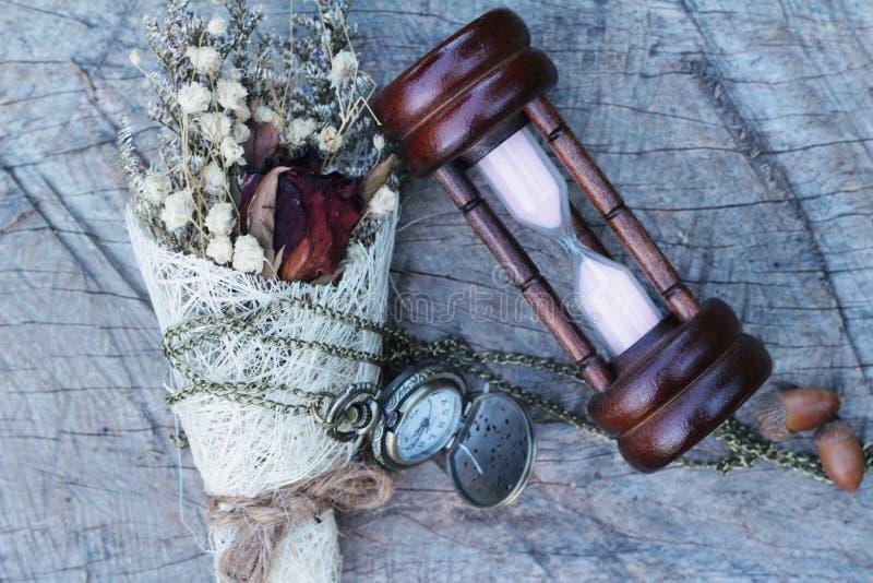 Orologio da tasca e clessidra antichi con i fiori secchi fotografia stock libera da diritti