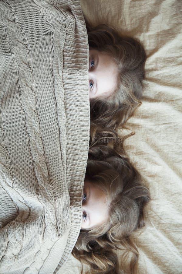 Orologio dei gemelli delle ragazze da sotto le coperte fotografia stock libera da diritti