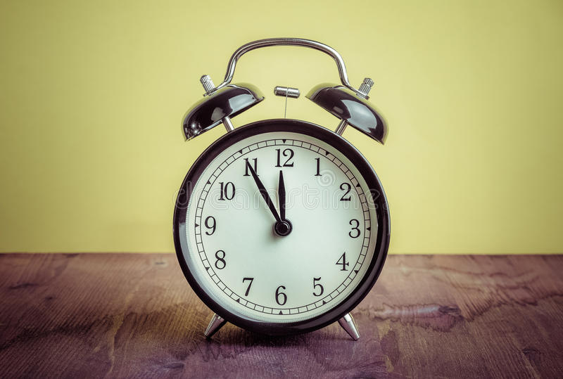 orologio del ` del ` s dodici o già, tempo di svegliare per pranzo, vecchia sveglia metallica nera d'annata fotografie stock libere da diritti
