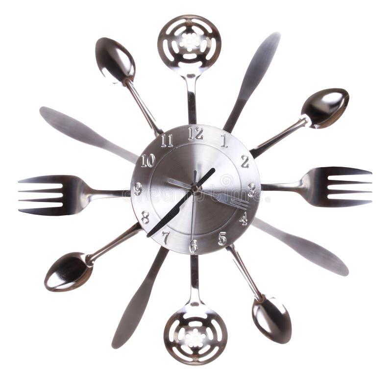 Orologio della cucina con i cucchiai e le forchette. Concetto. Passaggi di tempo in cucina immagini stock