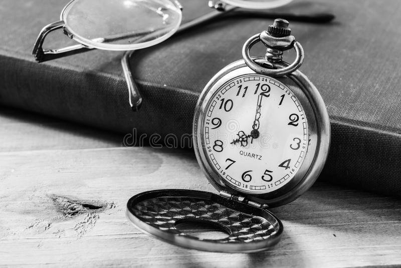 Orologio della tasca sul fondo dei libri immagine stock