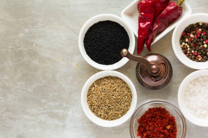 Orologio delle spezie Fresatura con i semi neri e verdi roventi dei piselli, del sale, della paprica, dei baccelli del peperoncin immagini stock libere da diritti