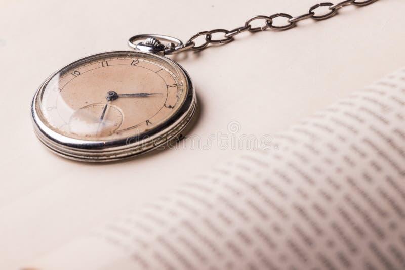 Orologio di decomposizione sui precedenti di vecchi libri saggi immagini stock libere da diritti