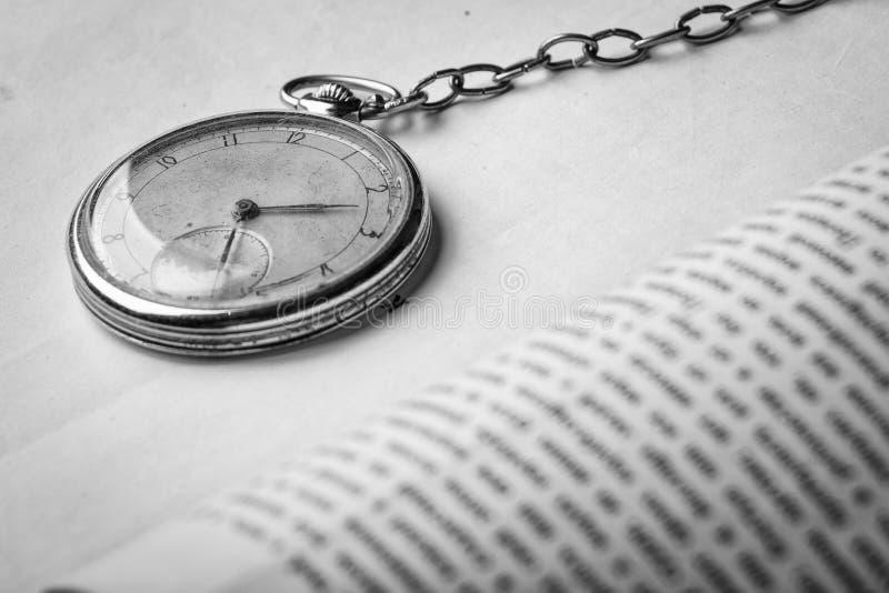 Orologio di decomposizione sui precedenti di vecchi libri saggi miseri fotografia stock libera da diritti