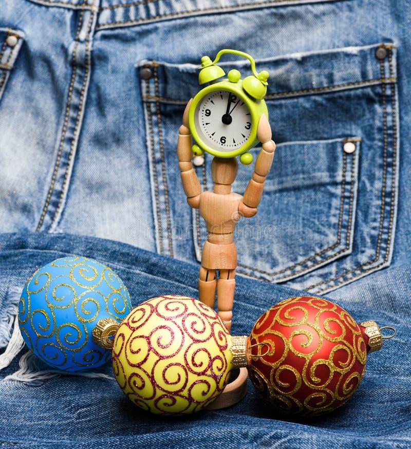 Orologio di legno della tenuta del giocattolo del corpo umano vicino alla palla della decorazione di natale Giocattoli decorativi immagini stock