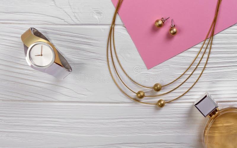 Orologio dorato e d'argento con la collana dorata su fondo di legno bianco fotografie stock libere da diritti