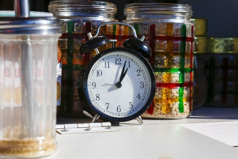Orologio e barattoli manuali su uno scaffale immagine stock