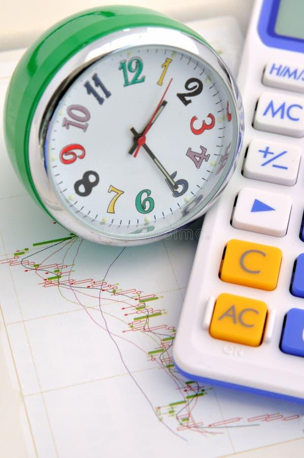 Orologio e calcolatore sul grafico di riserva fotografia stock