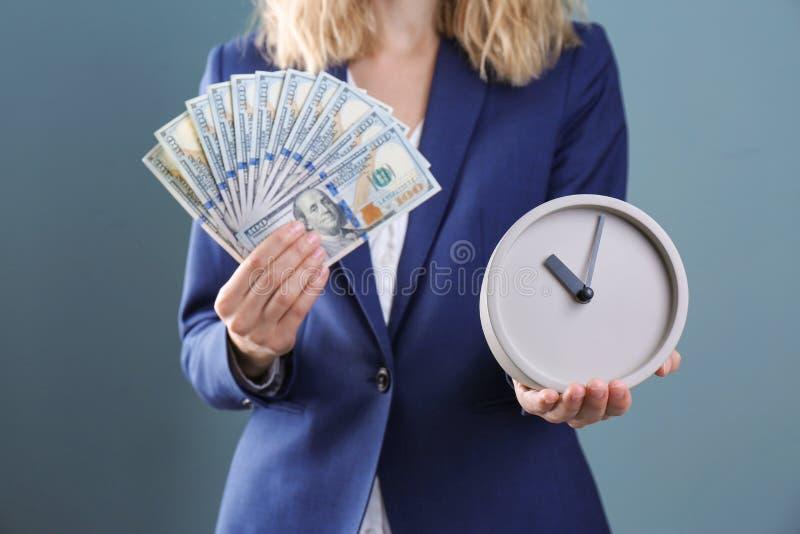 Orologio e soldi della tenuta della donna di affari sul fondo di colore Gestione di tempo immagine stock libera da diritti